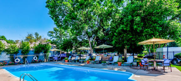 Pool deck with lounge chairs, tables, umbrellas and large trees in your background.