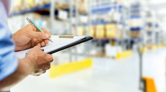 Person Checking Warehouse Inventory on Clipboard