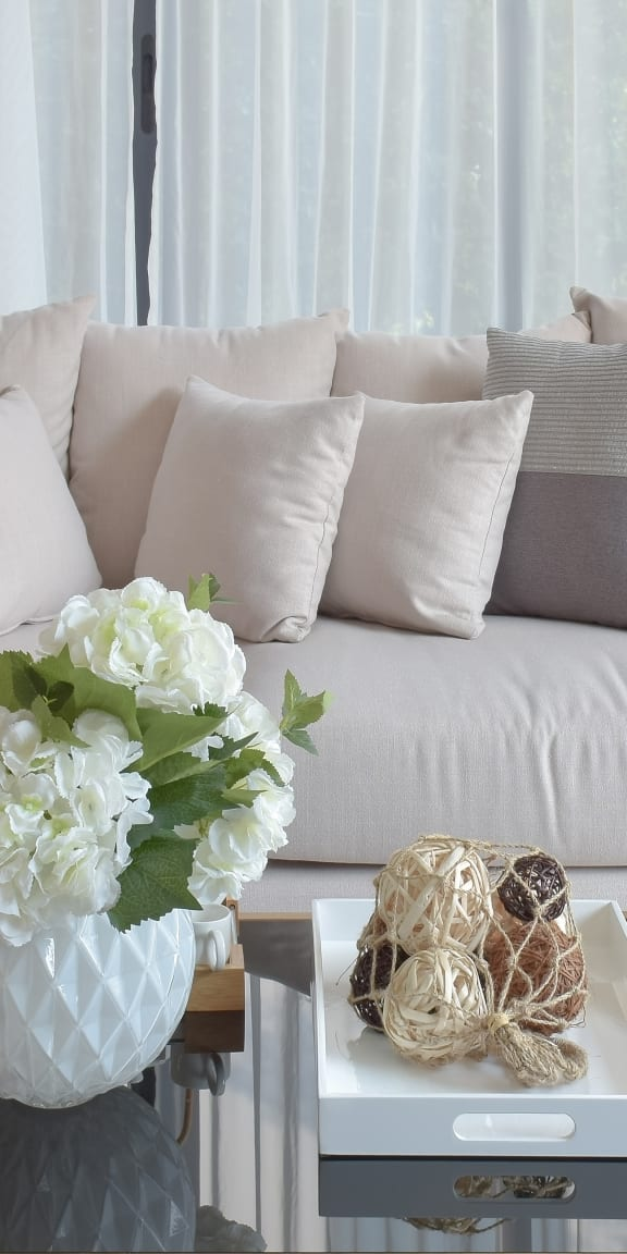 Couch next to window with throw pillows