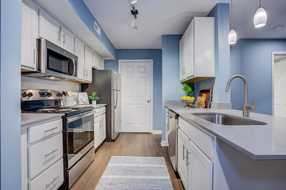 White kitchen cabinetry, quartz surfaces, and stainless steel appliances at Sunscape Apartments, near Carilion Hospital, VA