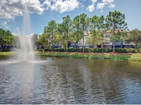 Pond with fountain with exterior of three story apartment buildings in the background