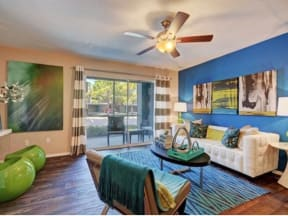 Furnished model living room area with sofa, accent chair, and coffee tables looking out to patio with sliding door.