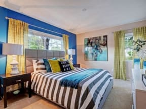 Furnished model bedroom with queen size bed, nightstands, lamps and dresser.