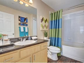 Furnished model bathroom with tile surround tub and extended vanity and sink.