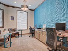 Business center with two computer stations and soft lounge seating