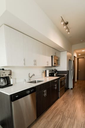 Apartments for Rent Seattle, WA - Apartment Entryway to Kitchen with Stainless Appliances, Modern Cabinetry, and Hardwood Flooring