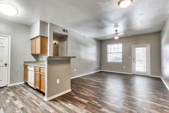 dining area over looking kitchen and living room. Brown/grey wood style flooring through out, kitchen with white appliances, brown cabinets, grey counter tops, patio door and window in living room