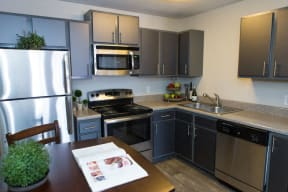 The Southern Apartments Kitchen with Stainless Steel Appliances, Ample Cabinet Storage, and Wood-Style Flooring