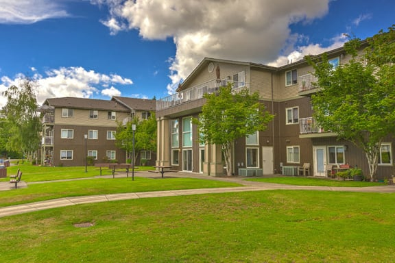 Building exterior and green grass | Vintage at Arlington Senior Apts for rent