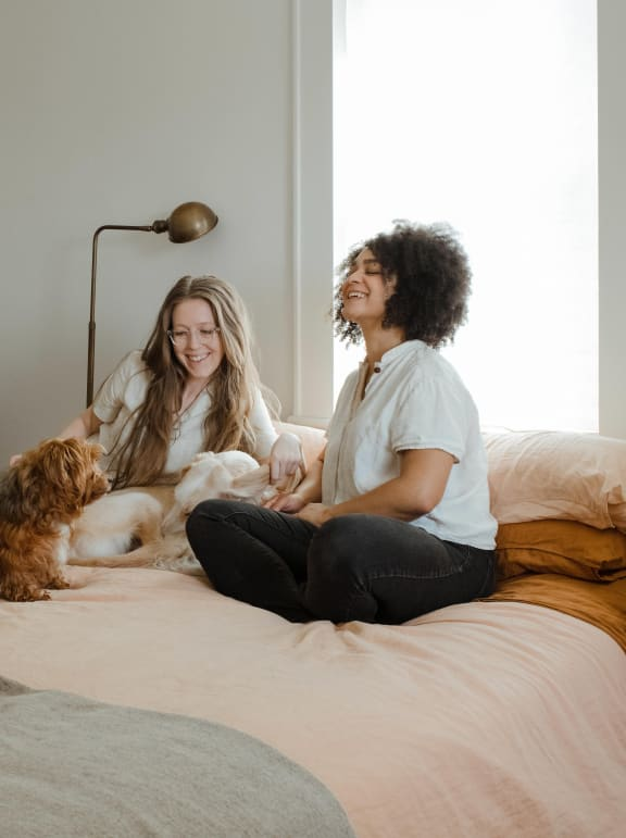 Two Women Sitting on Bed with Dog and Smiling and Laughing