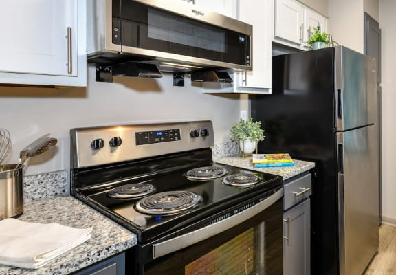 upgraded kitchen with granite countertops, stainless steel appliances, and hardwood-style floor