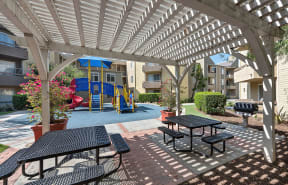 Covered seating by playground l Enclave apartments in Paramount CA
