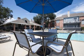 Resort Style Swimming Pool with Outdoor Dining Table and Lounge Chairs