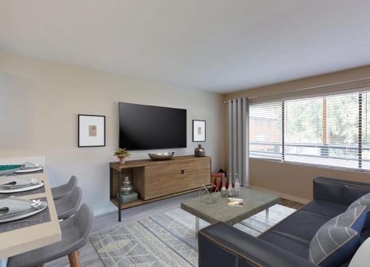 Staged living room with mounted TV, TV stand, coffee table, and large window.