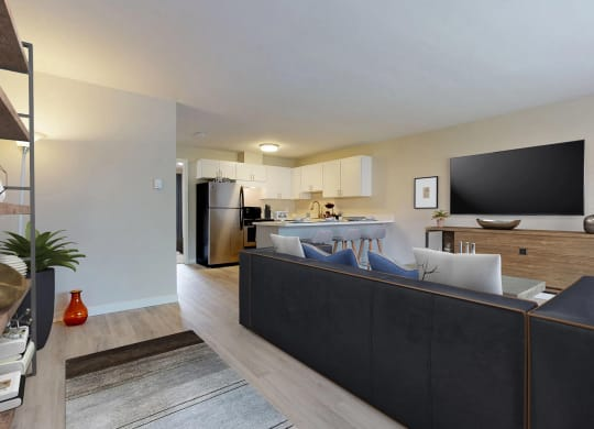 Staged, open layout living space that flows into an L-shaped Kitchen. Living room contains large sofa sectional.