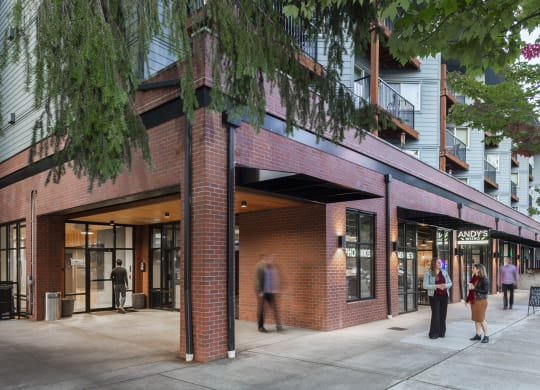 Corner exterior with trees, balconies, and people outside retail spaces