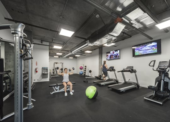 Gym with treadmills, an elliptical, weight machines, free weights, benches, an exercise ball and tvs