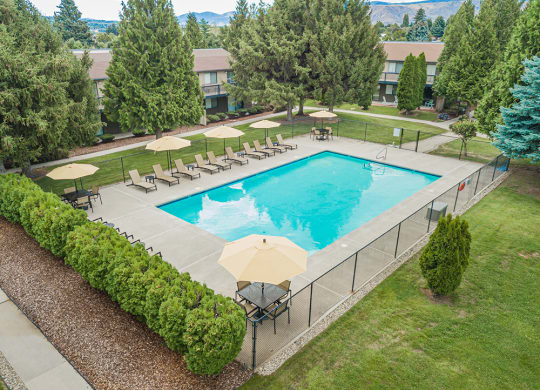 Large outdoor pool with ample pool seating and fence surrounding it.