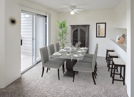 Dining area with table and chairs in the center, a ceiling fan with light, sliding glass doors to the left and a breakfast bar on the right.