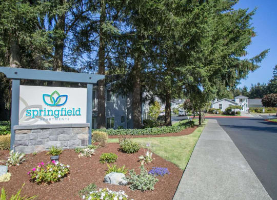 Exterior entry with trees and other plants.  There is a Springfield welcome sign.