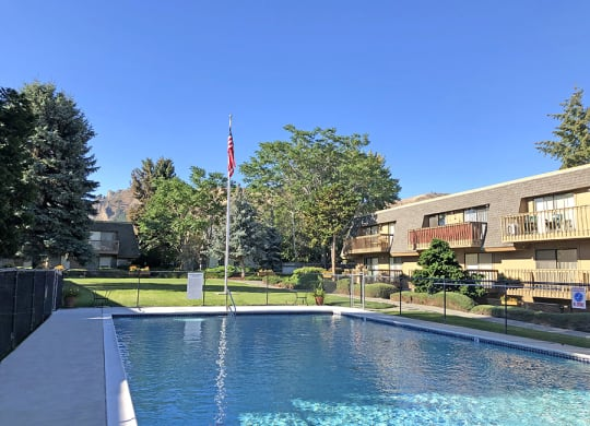 Large pool surrounded by grand and fencing in the courtyard of the property.