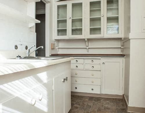 Kitchen with a sink, lots of counterspace and glass panel cabinet doors.
