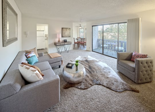 Living room with couch, chair, coffee table, and rug.  Sliding glass door opens to balcony with table and chairs.  Glimpse of the kitchen and dining room.