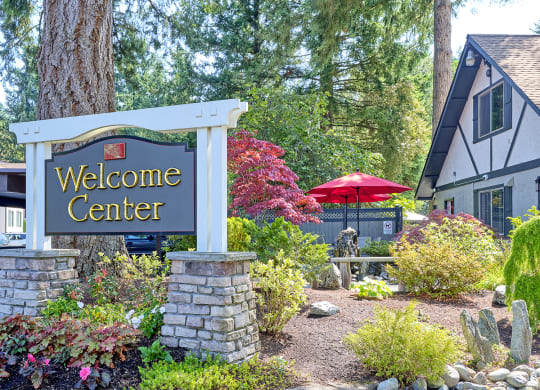 Large welcome center sign with trees, bushes, and flowers.