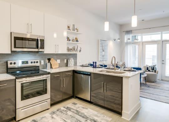 Kitchen attached to living room at Link Apartments® Grant Park, Atlanta, GA