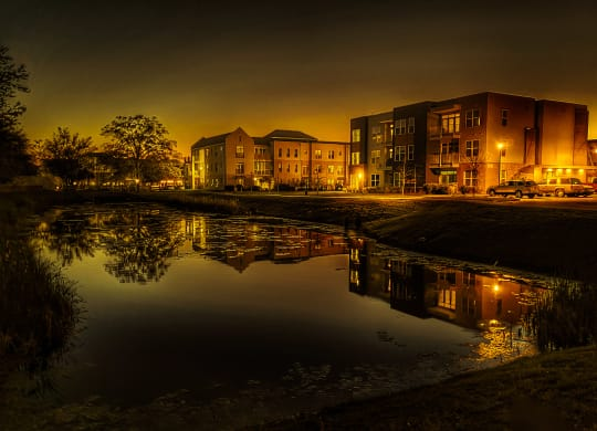 evening photo of apartment buildings and pond
