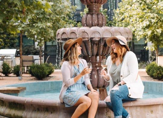 Two women sitting at courtyard fountain