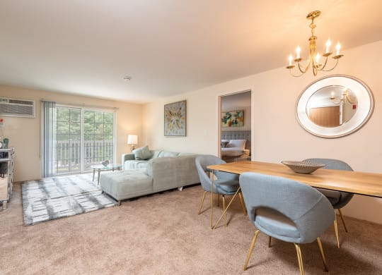 Two bedroom common area living room with balcony and dining space with plush carpeting