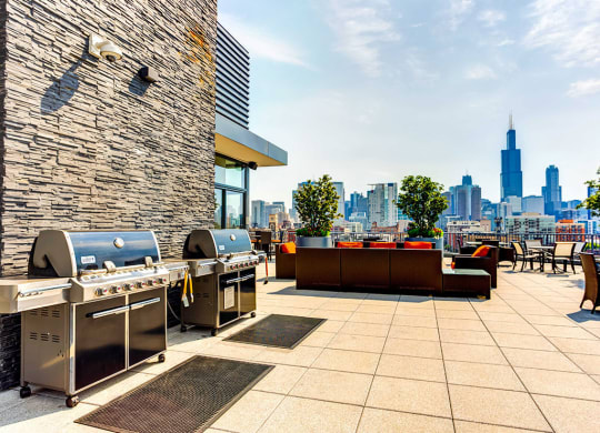 Outdoor grilling area with lounge seating and a skyline view at The Madison at Racine, Chicago, 60607