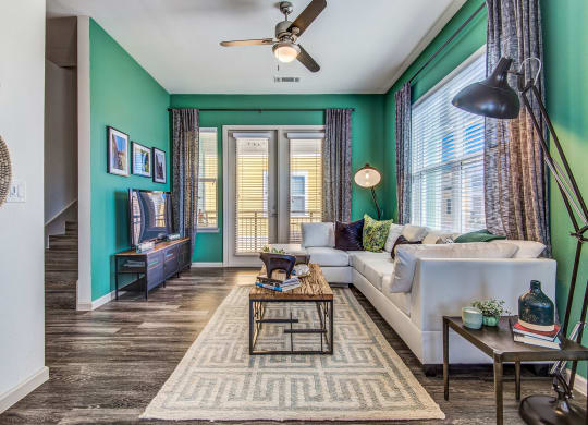 Lewisville TX Apartments - Open Space Living Room with Hardwood Floors, Stylish Interiors, and Door that Leads to a Balcony