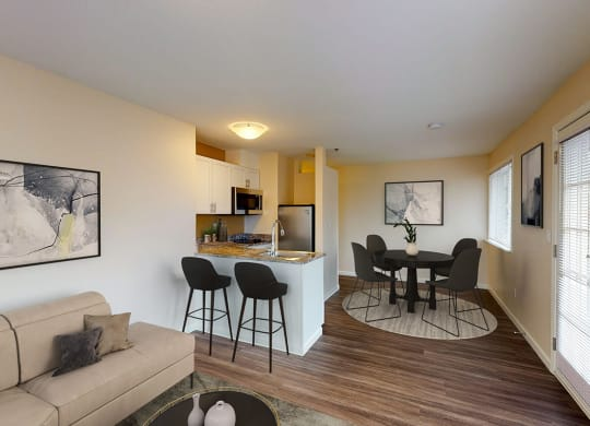 Open layout of the living, dining and kitchen area. Kitchen has a peninsula with 2 bar stools into the living area. To the right of the kitchen is the dining area with a round dining table and 4 chairs. Hard wood style flooring throughout.
