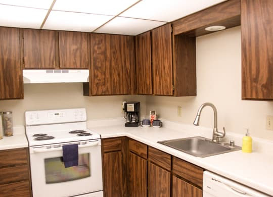 L shaped kitchen with brown cabinets, white applianced and stainless steel sink.
