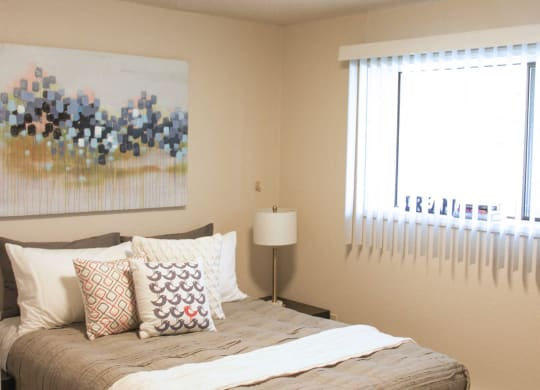 Bedroom with queen sized bed and large window with blinds.