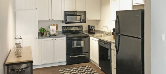 Corner Shaped Kitchen with white cabinets and black appliances. Appliances from left to right include stove and oven, microwave, dishwasher, and fridge.