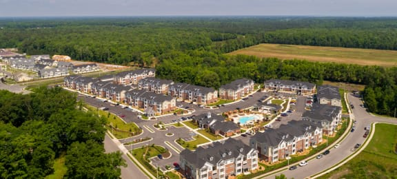 Overhead view of apartment buildings, clubhouse and pool; community is surrounded by trees and grass