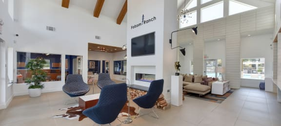 Community Leasing Office Lounge Area with Hardwood Inspired Floor, Blue Chairs and Mounted Flat Screen TV,