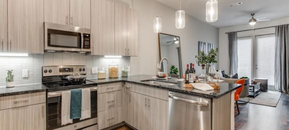 Grapevine TX Apartments - Modern Kitchen With Gray Cabinets, Black Granite Countertops, and Stainless Steel Appliances
