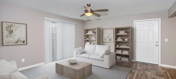 Model living room with wood floor and glass door to balcony