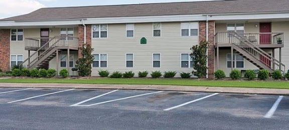 Exterior image of Hallmark Gardens. Shows asphalt parking lot in front of buildings with yellow siding and red brick, stairs leading to second level with red doors.