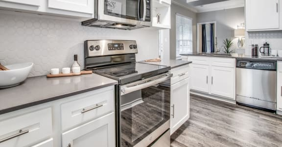 North Dallas TX Apartments- Spacious Modern Kitchen With Gray Granite Countertops, White Cabinets, and Stainless Steel Appliances