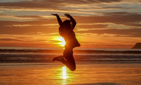 Girl jumping on beach in sunset