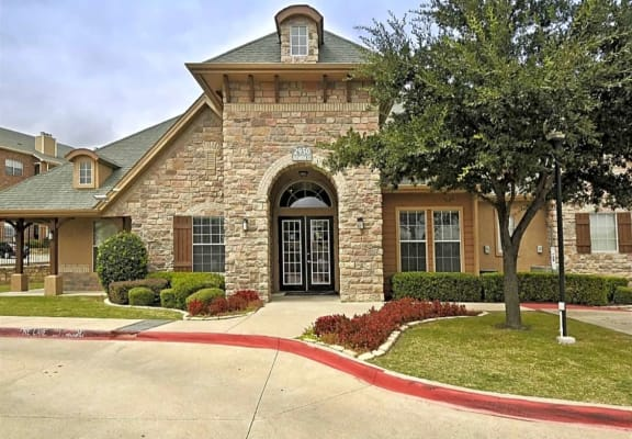 Building exterior with hedges and trees at The Life at Westland Estates, Texas, 76108