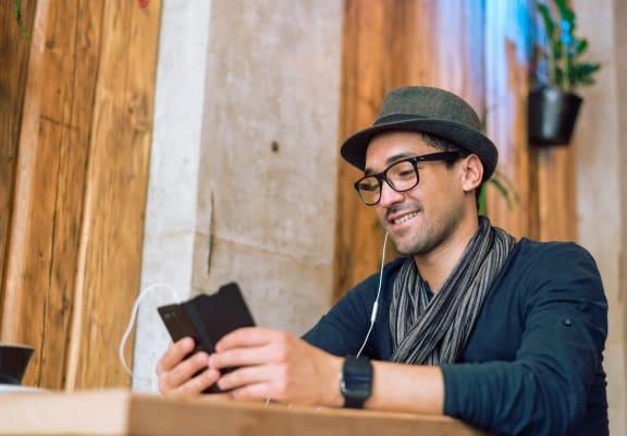Man Sitting At Table Looking at Smartphone