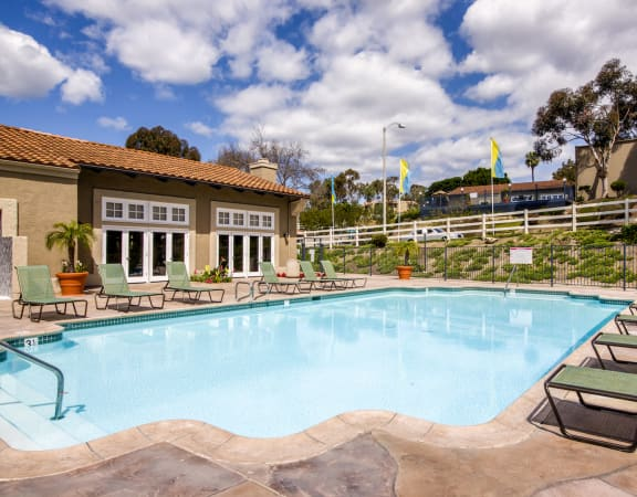 Carlsbad Apartments for Rent-Santa Fe Ranch Gated Pool With Lounge Chairs And Surrounding Brown Stone