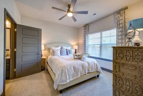 Primary bedroom with large windows and ceiling fan