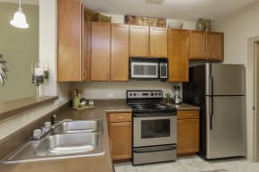 The Grove at Waterford Crossing Kitchen with Black/Stainless Steel Appliances, Wood Cabinets, and Access to Living Room
